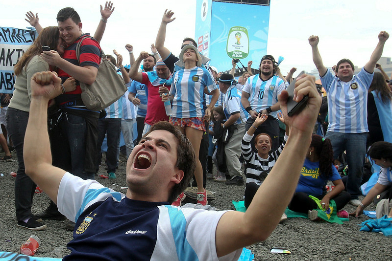 . Argentine soccer fans celebrate after watching their side score a goal, via a live telecast of the World Cup group F match between Argentina and Nigeria, inside the FIFA Fan Fest area, in Porto Alegre, Brazil, Wednesday, June 25, 2014. (AP Photo/Nabor Goulart)