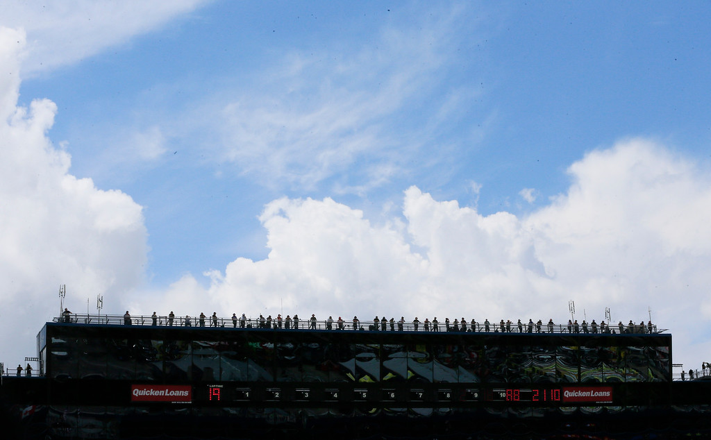 . Spotters lookout for their drivers atop the press center during the NASCAR Sprint Cup series auto race at Michigan International Speedway, Sunday, June 14, 2015, in Brooklyn, Mich. (AP Photo/Carlos Osorio)