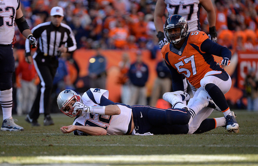 . New England Patriots quarterback Tom Brady (12) is sacked by Denver Broncos defensive end Jeremy Mincey (57) in the fourth quarter. The Denver Broncos take on the New England Patriots in the AFC Championship game at Sports Authority Field at Mile High in Denver on January 19, 2014. (Photo by AAron Ontiveroz/The Denver Post)