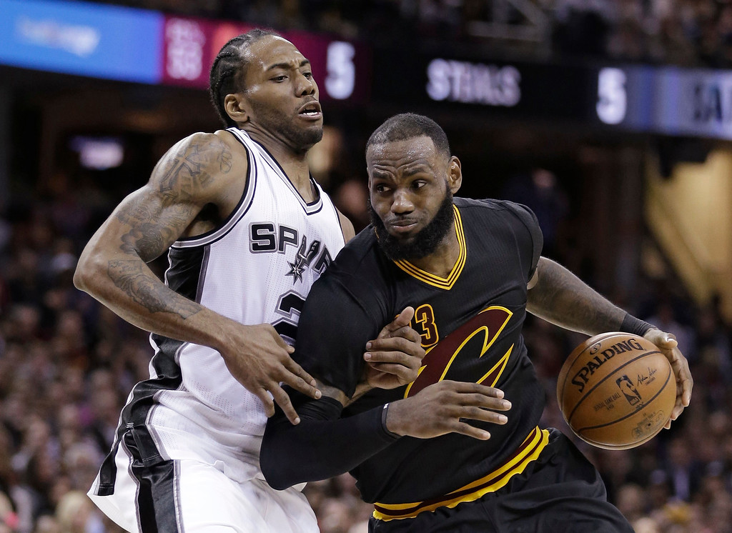 . Cleveland Cavaliers\' LeBron James, right, drives against San Antonio Spurs\' Kawhi Leonard during the second half of an NBA basketball game, Saturday, Jan. 21, 2017, in Cleveland. The Spurs won 118-115 in overtime. (AP Photo/Tony Dejak)