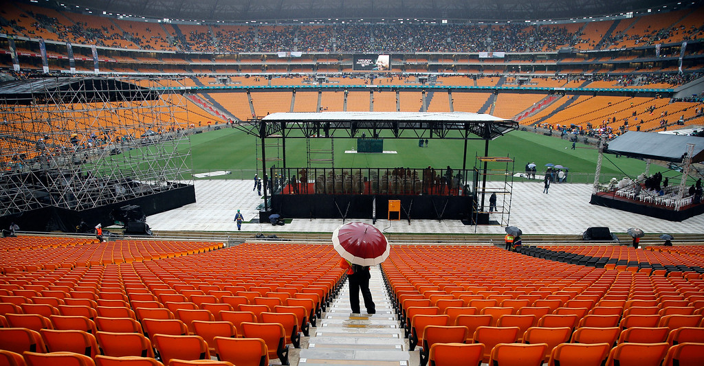 . A security personnel shelters from the rain under an umbrella as they stand behind the stage ahead of the memorial service for former South African president Nelson Mandela at Soccer City stadium in  Johannesburg in Johannesburg, South Africa, Tuesday, Dec. 10, 2013. (AP Photo/Themba Hadebe)