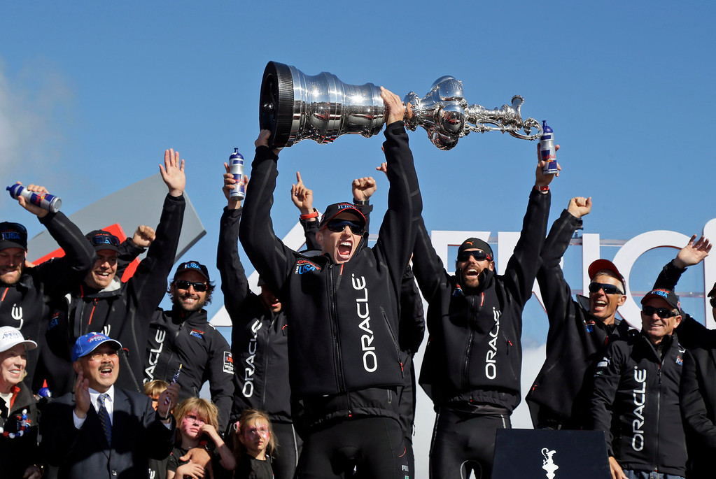 . Oracle Team USA skipper Jimmy Spithill holds up the Auld Mug as they celebrate in the podium after winning the America\'s Cup sailing event over Emirates Team New Zealand on Wednesday, Sept. 25, 2013, in San Francisco. (AP Photo/Marcio Jose Sanchez, File)