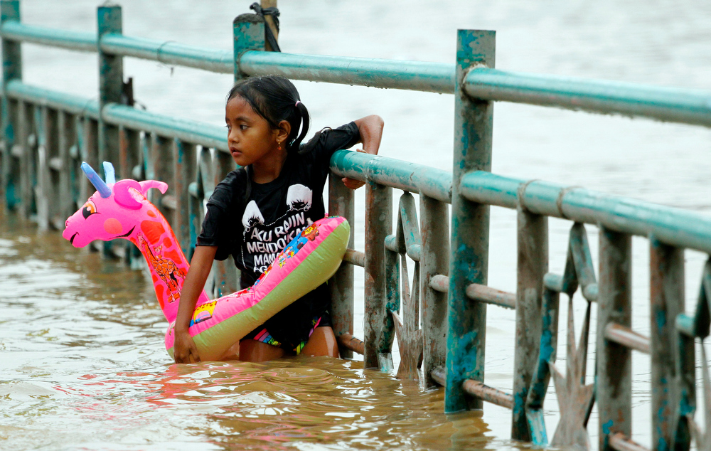 Description of . A girl holds a swimming ring while wading through floodwaters in Jakarta, Indonesia, Wednesday, Jan. 16, 2013. Flooding caused by monsoon rains have forced thousands of people to flee their homes in Indonesia\'s capital.  (AP Photo/Achmad Ibrahim)