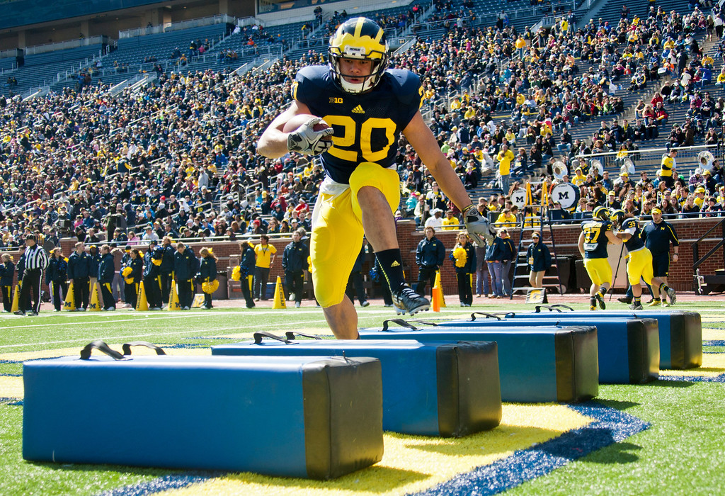 . Michigan running back Drake Johnson (20) steps through an obstacle drill during the football team\'s annual spring game, Saturday, April 5, 2014, in Ann Arbor, Mich. (AP Photo/Tony Ding)