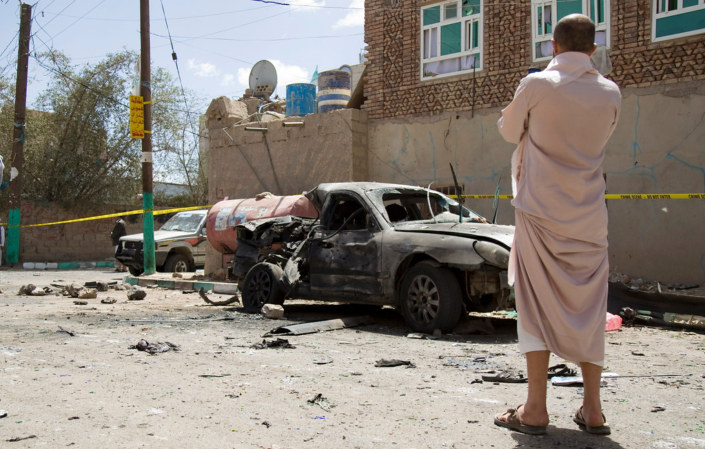 . A man looks at a damaged car after a suicide attack in Sanaa, Yemen, Friday, March 20, 2015. Triple suicide bombers hit a pair of mosques crowded with worshippers in the Yemeni capital, Sanaa, on Friday, causing heavy casualties, according to witnesses. The attackers targeted mosques frequented by Shiite rebels, who have controlled the capital since September. (AP Photo/Hani Mohammed)