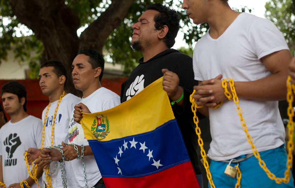 Description of . Venezuelan students pray as they chain themselves to each other during a demonstration near the Cuban embassy in Caracas February 15, 2013. Opposition demonstrators protested outside the embassy in Caracas, demanding that Venezuela's President Hugo Chavez return to Venezuela and calling for more information about his condition. Chavez has not been seen in public for more than two months since undergoing cancer surgery in Havana on December 11.  REUTERS/Carlos Garcia Rawlins