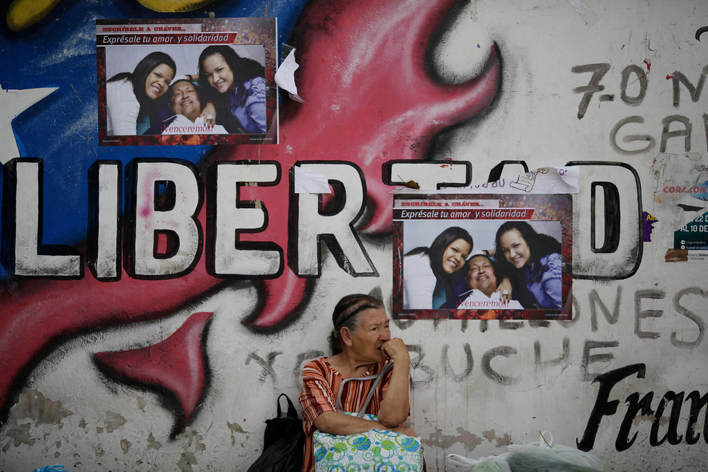 . A woman sits against a wall covered with pictures of Venezuela\'s President Hugo Chavez with his daughters Maria Gabriela, left, and Rosa Virginia in Caracas, Venezuela, Tuesday, Feb. 26, 2013. The government said last week that the country\'s ailing president was continuing unspecified medical treatments at the military hospital in Caracas. Chavez\'s sudden return to Venezuela after more than two months of cancer treatments in Cuba has fanned speculation that the president could be preparing to relinquish power and make way for a successor and a new election. (AP Photo/Ariana Cubillos)