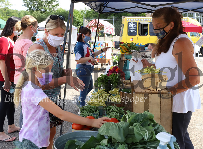 Pam Agnew and her daughter Alexa browse Cherry Valley Farm's stand at the Cranberry Farmers Marke Friday. Seb Foltz/Butler Eagle 0724