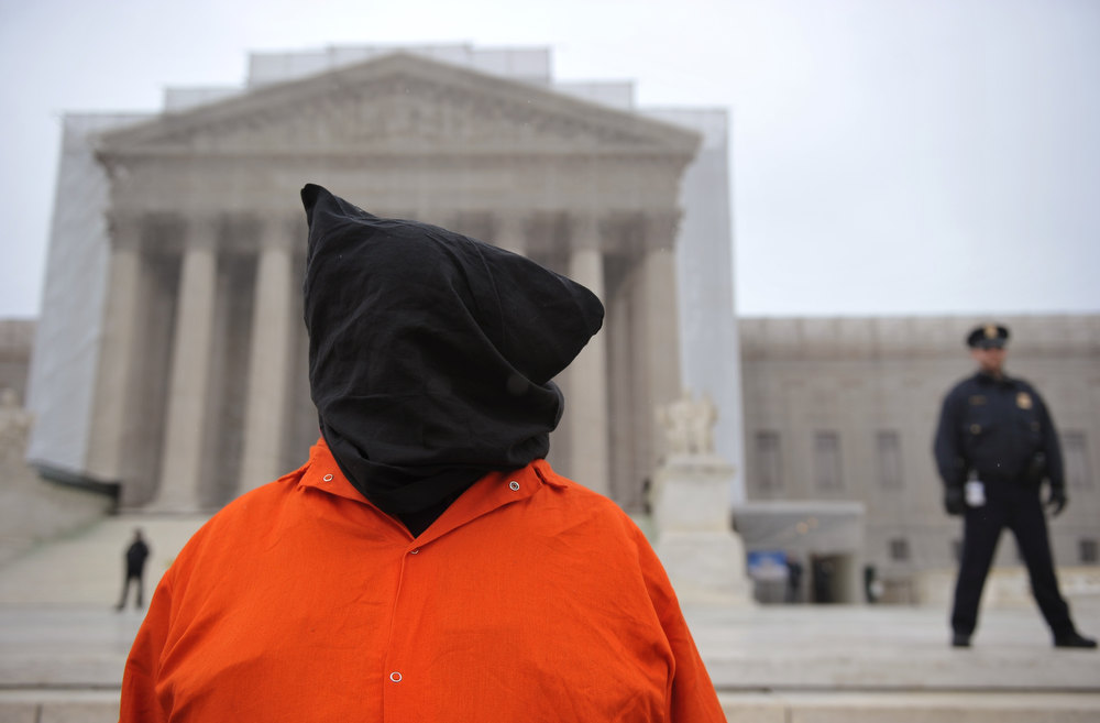 Description of . A hooded demonstrator takes part in a rally to call for the closing of the Guantanamo Bay detention center on January 11, 2013 in front of the US Supreme Court on Capitol Hill in Washington. MANDEL NGAN/AFP/Getty Images