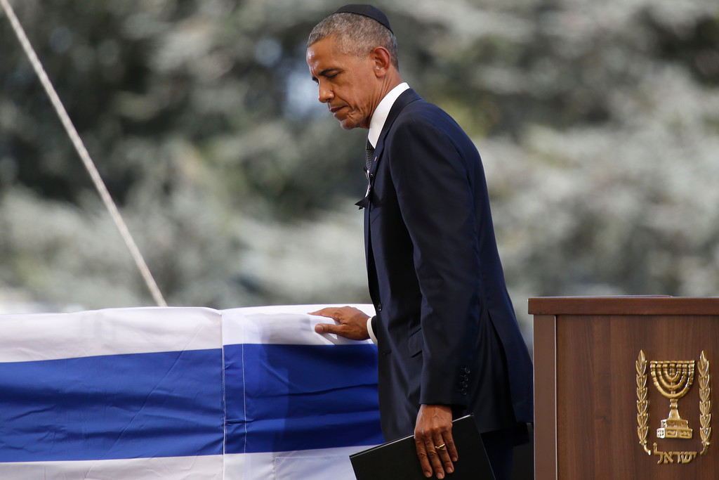 . U.S. President Barack Obama touches the flag-draped coffin of former Israeli President Shimon Peres during his funeral at the Mount Herzel national cemetery in Jerusalem, Friday, Sept. 30, 2016. (AP Photo/Ariel Schalit)