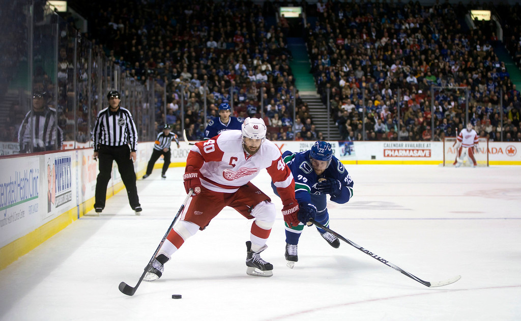 . Detroit Red Wings\' Henrik Zetterberg, left, of Sweden, moves the puck in the offensive zone while being chased by Vancouver Canucks\' Alexander Edler, of Sweden, during the first period of an NHL hockey game in Vancouver, British Columbia on Saturday, Jan.  3, 2015. (AP Photo/The Canadian Press, Darryl Dyck)