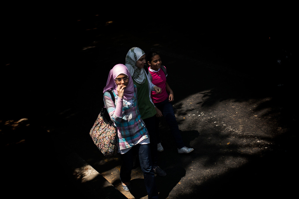 . Egyptian girls walk in the Zamalek district in Cairo, Egypt, Tuesday, Aug. 27, 2013.  The chairman of the Egyptian Airports Co. says some flights are arriving nearly empty to Egypt and that passenger traffic in the past week has fallen by half.(AP Photo/Manu Brabo)
