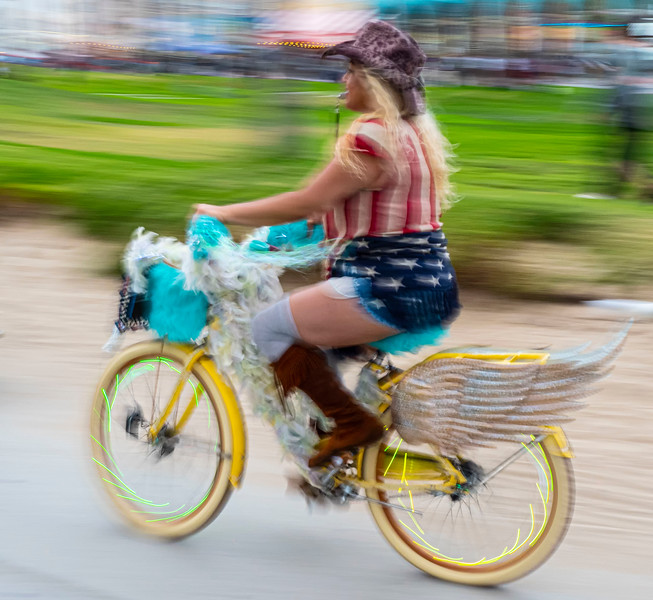 Flad adorned rider races along the boardwalk
