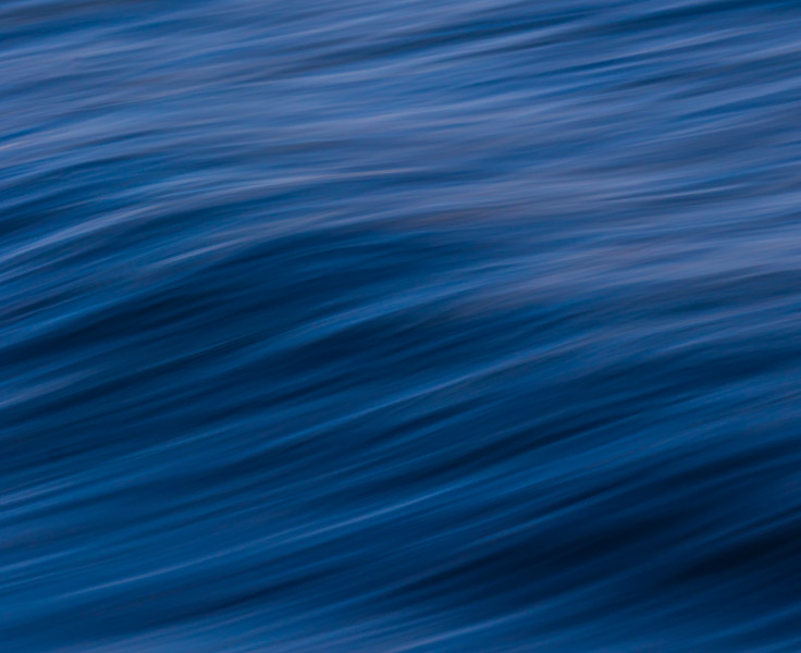 Abstract waves and sea shore in muted hues of blue