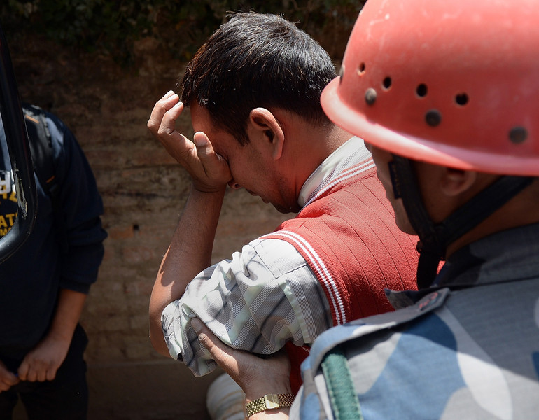 . A Nepalese resident reacts as police retrieve the body of his relative Prasamsah, 14, during rescue efforts in Balaju in Kathmandu on April 27, 2015. International aid groups and governments intensified efforts to get rescuers and supplies into earthquake-hit Nepal on April 26, 2015, but severed communications and landslides in the Himalayan nation posed formidable challenges to the relief effort. As the death toll surpassed 2,000, the US together with several European and Asian nations sent emergency crews to reinforce those scrambling to find survivors in the devastated capital Kathmandu and in rural areas cut off by blocked roads and patchy phone networks. PRAKASH SINGH/AFP/Getty Images