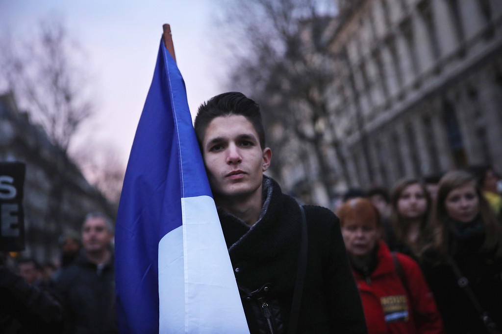 . PARIS, FRANCE - JANUARY 11:  Demonstrators make their way along Place de la Republique during a mass unity rally following the recent terrorist attacks on January 11, 2015 in Paris, France. An estimated one million people have converged in central Paris for the Unity March joining in solidarity with the 17 victims of this week\'s terrorist attacks in the country. French President Francois Hollande led the march and was joined by world leaders in a sign of unity. The terrorist atrocities started on Wednesday with the attack on the French satirical magazine Charlie Hebdo, killing 12, and ended on Friday with sieges at a printing company in Dammartin en Goele and a Kosher supermarket in Paris with four hostages and three suspects being killed. A fourth suspect, Hayat Boumeddiene, 26, escaped and is wanted in connection with the murder of a policewoman  (Photo by Dan Kitwood/Getty Images)