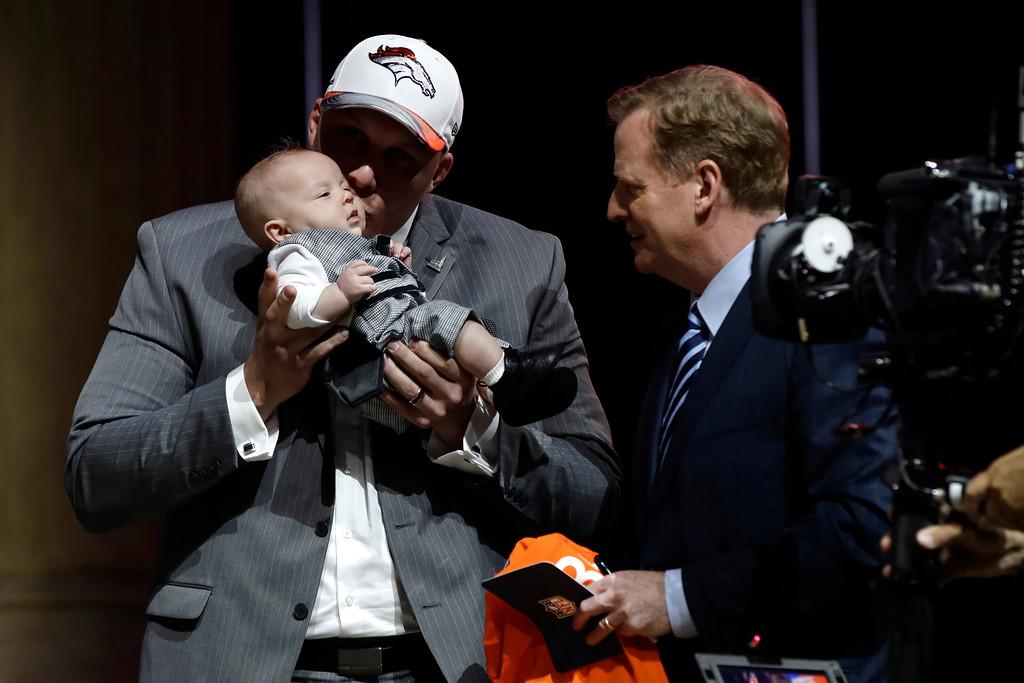 . Utah\'s Garett Bolles, left, kisses his son, Kingston, alongside NFL commissioner Roger Goodell after being selected by the Denver Broncos during the first round of the 2017 NFL football draft, Thursday, April 27, 2017, in Philadelphia. (AP Photo/Matt Rourke)
