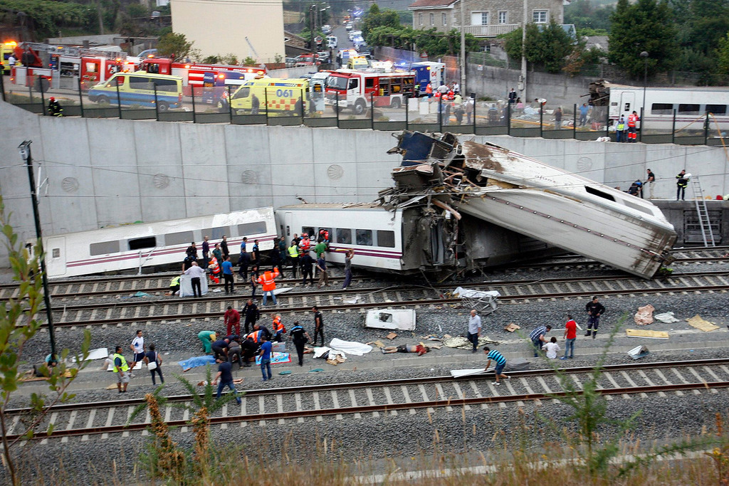 . Rescue workers pull victims from a train crash near Santiago de Compostela, northwestern Spain, July 24, 2013. At least 35 people were killed and 50 injured when a train derailed on the outskirts of the northern Spanish city of Santiago de Compostela on Wednesday in one of the country\'s worst rail disasters. Bodies covered in blankets lay next to carriages as smoke billowed from the wreckage a few hundred meters away from the entrance to the city\'s main station. REUTERS/Oscar Corral