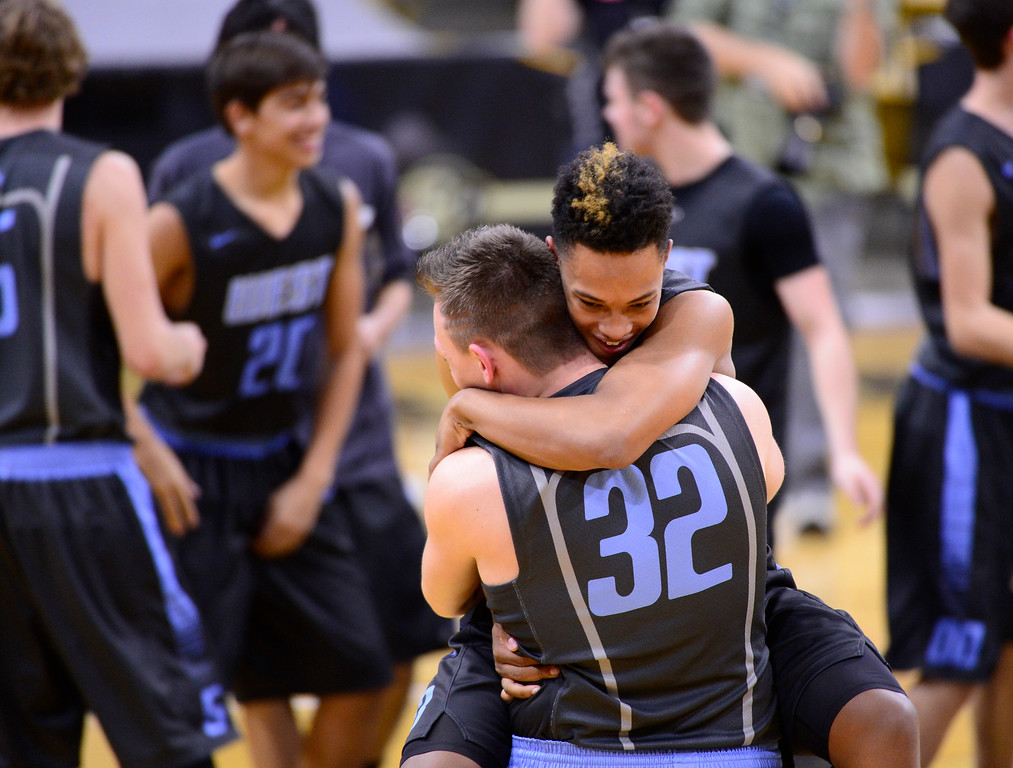 . Pierre Taylor (13) jumps in the arms to hug Dean Thompson (32) of Pueblo West Cyclones after their win at the Coors Events Center on March 12, 2016 in Boulder, Colorado. Pueblo West Cyclones defeated Valor Christian Eagles 70-51 to win the Colorado State 4A Boys Championship. (Photo by Brent Lewis/The Denver Post)