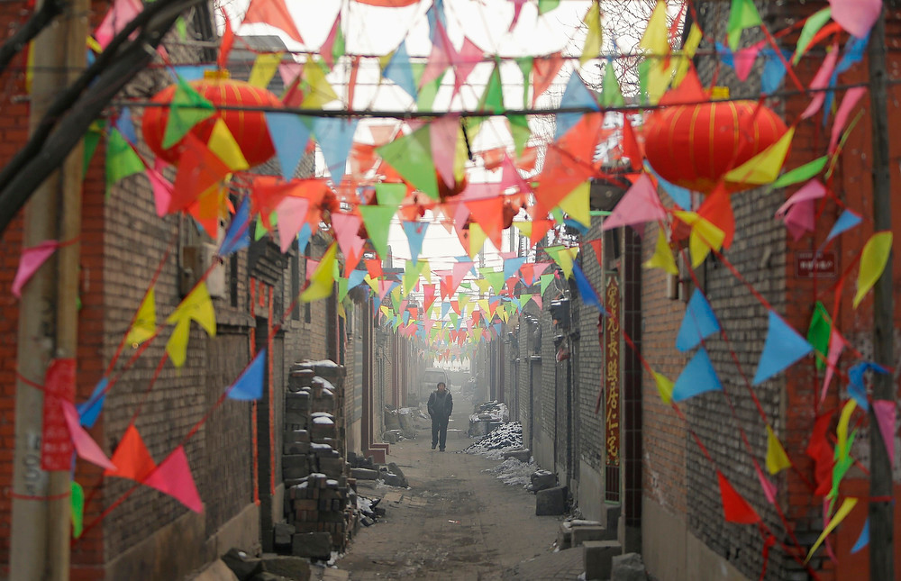 Description of . A villager walks along an alley decorated for Christmas ain the Liuhe village, near the city of Taiyuan, Shanxi province on December 24, 2012. REUTERS/Jason Lee