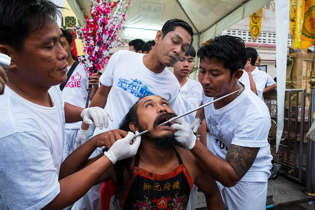 . A trio of attendants pierce a devotee\'s face with a steel spike outside Jui Tui Chinese Shrine on September 30, 2014 in Phuket, Thailand. (Photo by David Longstreath/Getty Images)