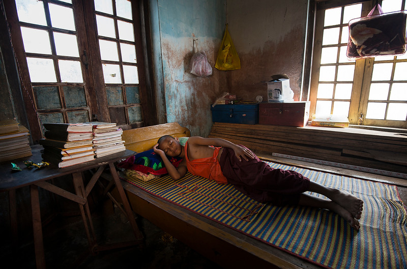 A young monk photographed in a corner of a  temple which he has turned into his bed room,  Nyauugshwe, Myanmar, 2017