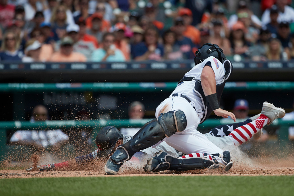 . Cleveland Indians Carlos Santana (41) dives in safe at home ahead of the tag by Detroit Tigers catcher James McCann (34) during the third inning in the first baseball game of a doubleheader in Detroit, Saturday, July 1, 2017. (AP Photo/Rick Osentoski)