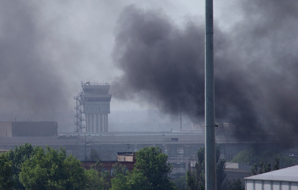 . Smoke rises from the airport outside Donetsk, Ukraine, Monday, May 26, 2014. Ukraine\'s military launched airstrikes Monday against the separatists who had taken over the airport in the eastern city of Donetsk, suggesting that fighting in the east is far from over. (AP Photo/Ivan Sekretarev)