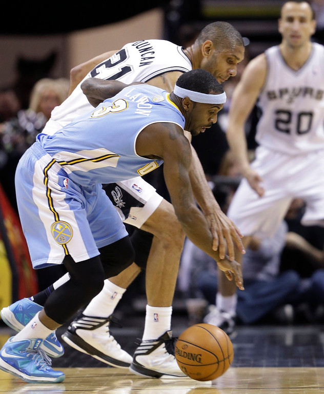 . San Antonio Spurs\' Tim Duncan (21) and Denver Nuggets\' Ty Lawson (3) chase a loose ball during the first half of an NBA basketball game, Wednesday, March 27, 2013, in San Antonio. (AP Photo/Eric Gay)