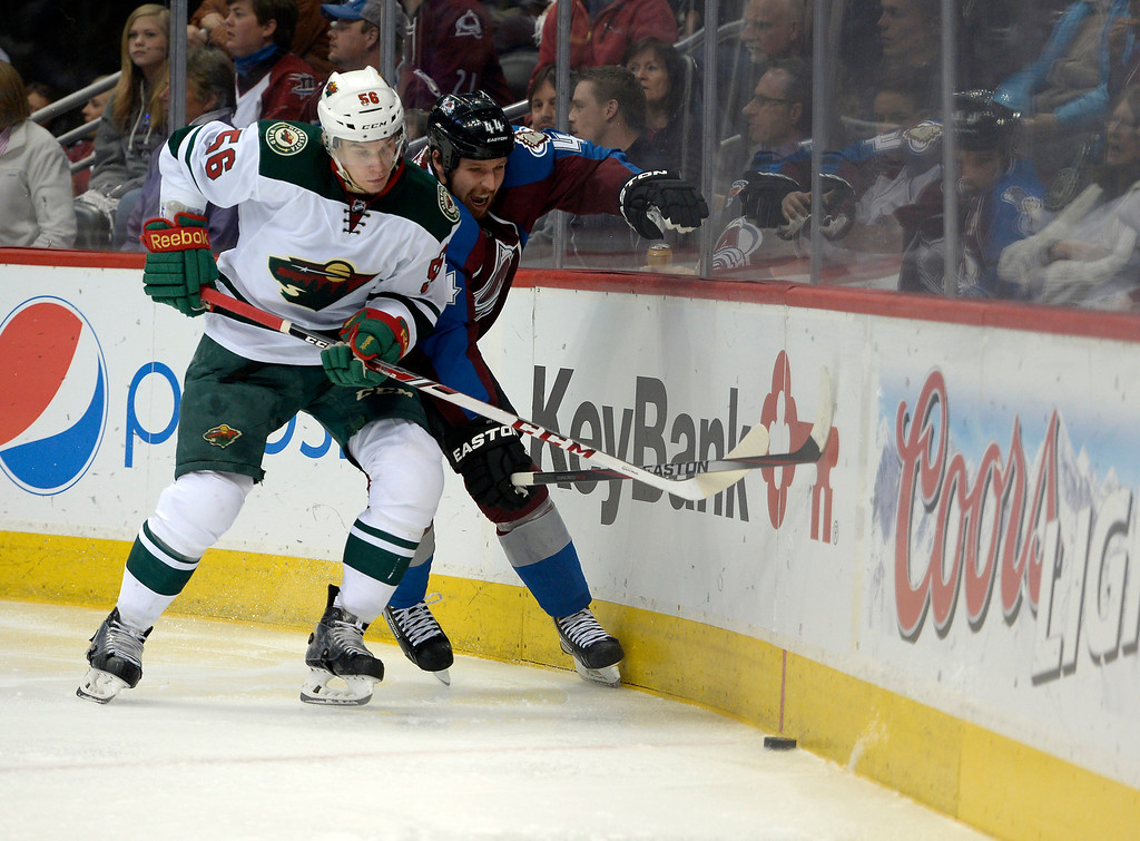 . DENVER, CO - APRIL 26: Minnesota Wild left wing Erik Haula (56) fights for the puck against the boards with Colorado Avalanche defenseman Ryan Wilson (44) behind the Minnesota Wild net during the third period of action. The Colorado Avalanche hosted the Minnesota Wild in the fifth round of the Stanley Cup Playoffs at the Pepsi Center in Denver, Colorado on Saturday, April 26, 2014. (Photo by John Leyba/The Denver Post)
