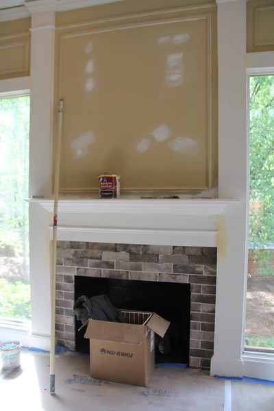 """the fireplace - all the """"gold"""" walls will be painted gray - the fireplace has gas logs and the brick facing is actually tile. They added 2 more rows, so are not finished with grout."""
