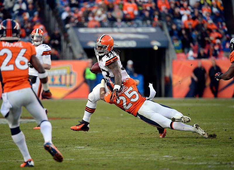. Cleveland Browns running back Trent Richardson (33) gains a yard against Denver Broncos cornerback Chris Harris (25) during the third quarter.  The Denver Broncos vs Cleveland Browns at Sports Authority Field Sunday December 23, 2012. Joe Amon, The Denver Post