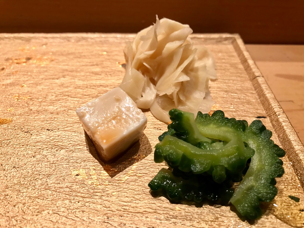 Palate cleansers - an eye-opening salted bitter gourd pickle, a creamy cube of tofu, pickled ginger.