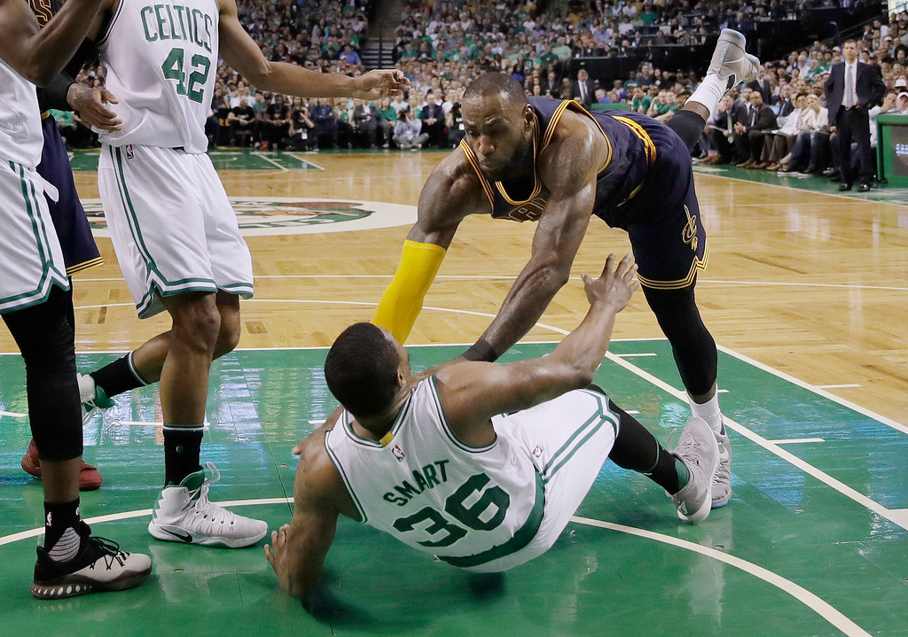 . Cleveland Cavaliers forward LeBron James, right, falls to the floor with Boston Celtics guard Marcus Smart during the second quarter of Game 1 of the NBA basketball Eastern Conference finals, Wednesday, May 17, 2017, in Boston. (AP Photo/Charles Krupa)