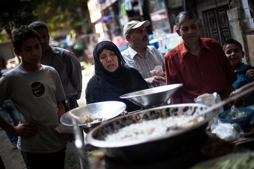 . An Egyptian woman waits for her breakfast on a street fast food restaurant in Suleiman Gohar market in Dokki district in Cairo, Egypt, Monday, Aug. 26, 2013. Egypt\'s recent turmoil has scared away tourists and affected the livelihood of the one in eight Egyptians who earn their living from tourism. An evening curfew imposed by the military to quell protests has further choked many businesses, such as restaurants, stores and entertainment venues, serving another blow to the country\'s already battered economy.  (AP Photo/Manu Brabo)