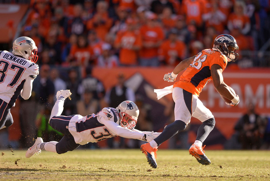 . Denver Broncos wide receiver Demaryius Thomas (88) runs away from New England Patriots free safety Devin McCourty (32) during the second quarter. The Denver Broncos vs. The New England Patriots in an AFC Championship game  at Sports Authority Field at Mile High in Denver on January 19, 2014. (Photo by John Leyba/The Denver Post)