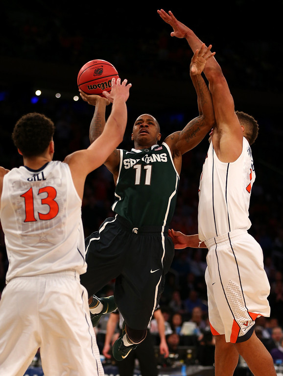 . Keith Appling #11 of the Michigan State Spartans goes to the basket against Anthony Gill #13 of the Virginia Cavaliers during the regional semifinal of the 2014 NCAA Men\'s Basketball Tournament at Madison Square Garden on March 28, 2014 in New York City.  (Photo by Elsa/Getty Images)