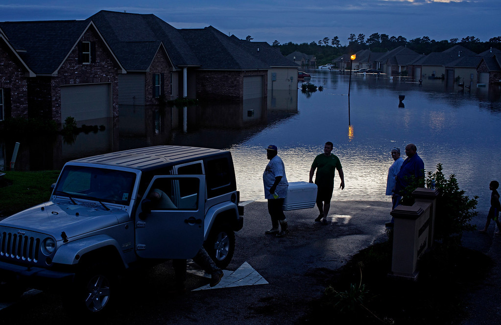 . Residents evacuate with food in ice chests on Providence Boulevard in Hammond, La., where flood waters inundated homes after heavy rains in the region Saturday, Aug. 13, 2016. (AP Photo/Max Becherer)