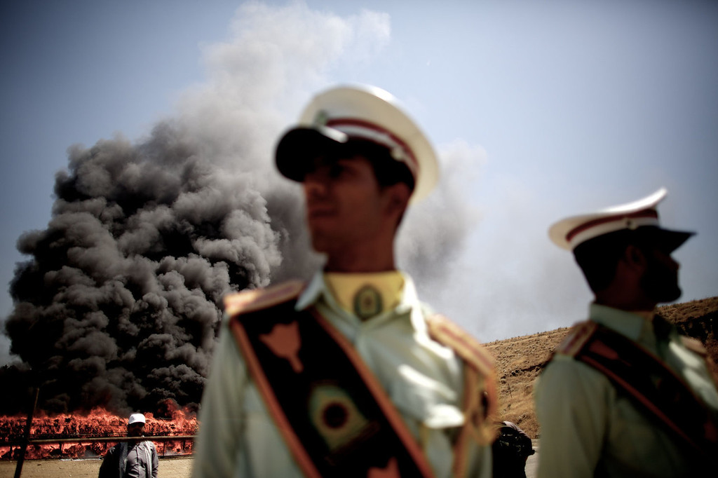 . Iranian policemen stand guard as 50 tons of drugs seized in recent months burn in eastern Tehran on June 26, 2013 to mark the International Day Against Drug Abuse and Illicit Trafficking.  BEHROUZ MEHRI/AFP/Getty Images