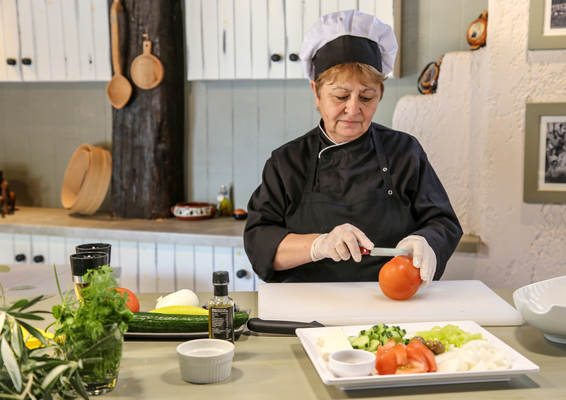 lady slicing a tomato in a kitchen