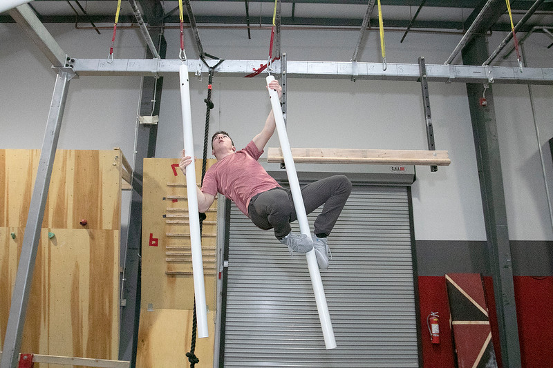 Jonathan Godbout, 15, from Sterling showed off some of the  obstacles he trains on at Ultimate Obstacles in West Boylston on Wednesday, Feb. 27, 2020. This obstacle had no name but he you had to move from one side of the room to the other only using these to tubes and hooks. SENTINEL & ENTERPRISE/JOHN LOVE