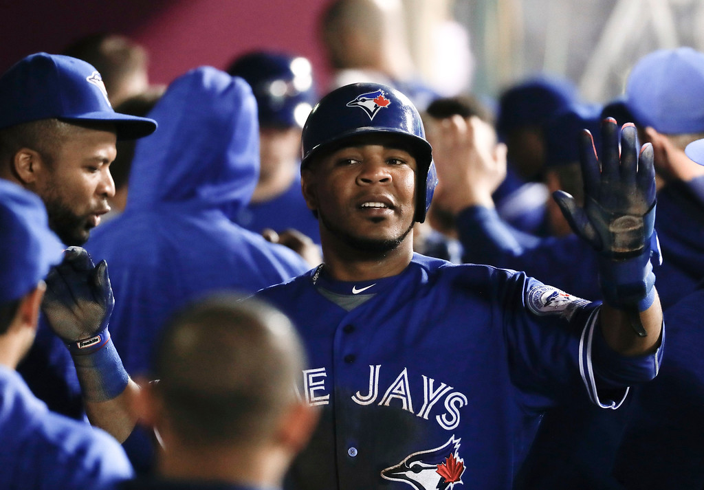 . Toronto Blue Jays\' Edwin Encarnacion, celebrates in the dugout after scoring on a sacrifice fly by Russell Martin during the fourth inning of a baseball game against the Los Angeles Angels in Anaheim, Calif., Thursday, Sept. 15, 2016. (AP Photo/Chris Carlson)
