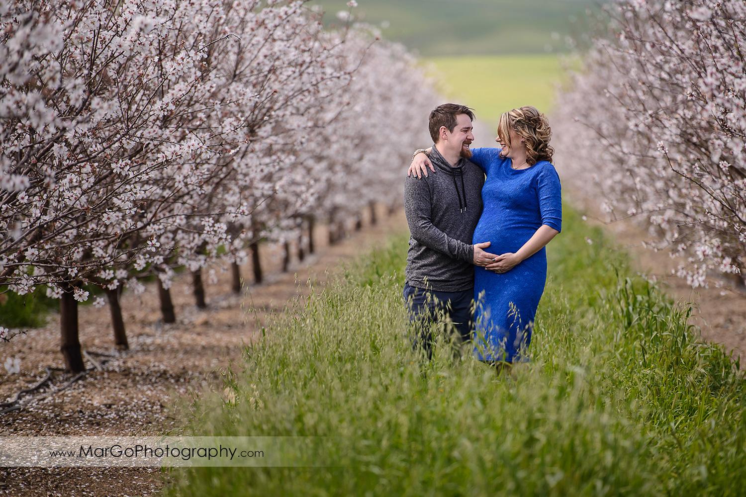 couple smiling at each other, Tracy orchard maternity session