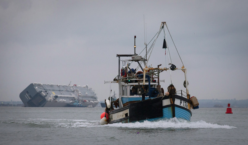 . A fishing boat passes the stricken vessel \'Hoegh Osaka\' after it ran aground on a sand bank in the Solent on January 5, 2015 in Cowes, England.  According to the owners of the Hoegh Osaka, the 52,000 ton cargo ship which is carrying 1,400 cars, some of which are thought to include Rolls Royces and Bentleys and is now stricken off the Isle of Wight, was deliberately grounded to prevent it from capsizing after it began listing as it left port. The ship became grounded on Bramble Bank in the Solent on Saturday night, forcing emergency services to rescue all 25 crew members on board.  (Photo by Matt Cardy/Getty Images)