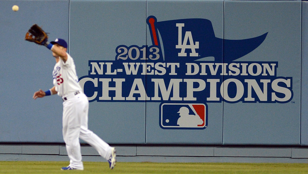 . The Dodgers\' Skip Schumaker #55 makes a catch in front of the new NL-West Championship banner during their game against the Rockies at Dodgers Stadium Saturday, September 28, 2013. (Photo by Hans Gutknecht/Los Angeles Daily News)