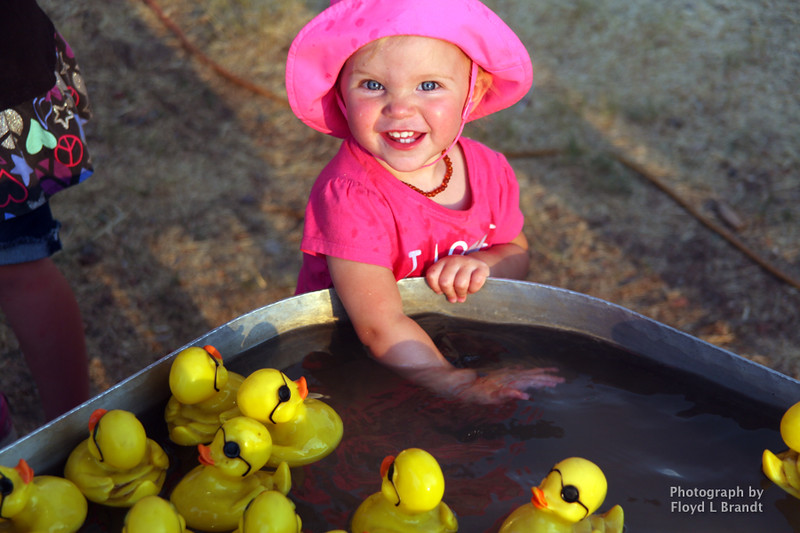 Havre Daily News / Floyd Brandt  Cool water and rubber ducks brings a smile to 18 mouth old Jaida Ophus's face at The Great Northern Fair in Hill County Thursday