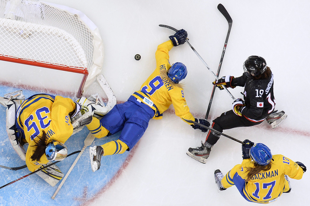 . Sweden\'s Josefine Holmgren (C) fights for the puck with Japan\'s Miho Shishiuchi during the Women\'s Ice Hockey Group B match Sweden vs Japan at the Shayba Arena during the Sochi Winter Olympics on February 9, 2014.    ANDREJ ISAKOVIC/AFP/Getty Images