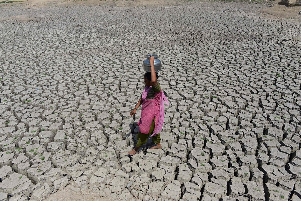 . An Indian woman walks on the parched bed of Chandola Lake with a metal pot on her head to fetch water in Ahmedabad on May 20, 2016. India is facing its worst water crisis in decades, with about 330 million people, or a quarter of the population, suffering from drought after two weak monsoons. / AFP PHOTO / SAM PANTHAKY/AFP/Getty Images