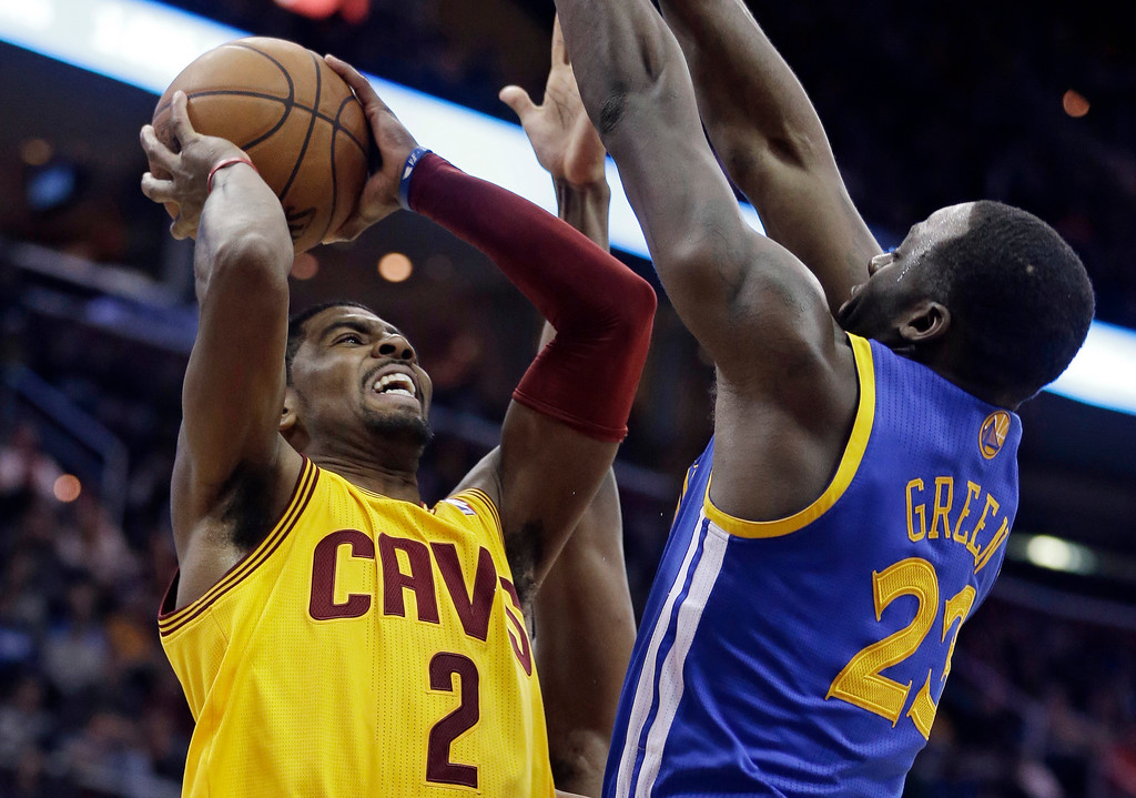 . Cleveland Cavaliers\' Kyrie Irving, left,  jumps to the basket against Golden State Warriors\' Draymond Green during overtime in an NBA basketball game Sunday, Dec. 29, 2013, in Cleveland. The Warriors defeated the Cavaliers 108-104 in overtime. (AP Photo/Tony Dejak)
