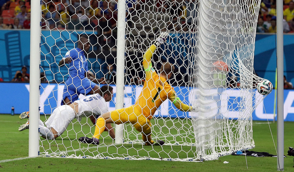 . Italy\'s Mario Balotelli (9) heads the ball past England\'s Gary Cahill (5) and goalkeeper Joe Hart (1) to score Italy\'s second goal during the group D World Cup soccer match between England and Italy at the Arena da Amazonia in Manaus, Brazil, Saturday, June 14, 2014. (AP Photo/Antonio Calanni)